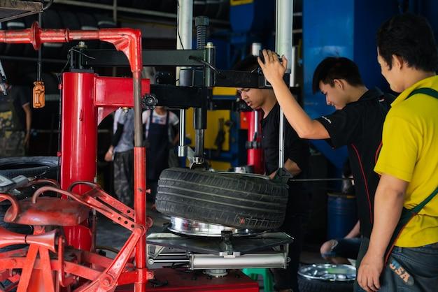Niezidentyfikowany Mechanik Samochodowy Lub Serwisant Demontaż I Sprawdzenie Chromowanej Felgi Samochodowej Premium Zdjęcia