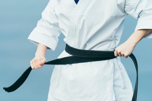 Nieznana Zawodniczka Karate Sznurująca Czarny Pas W Talii Premium Zdjęcia