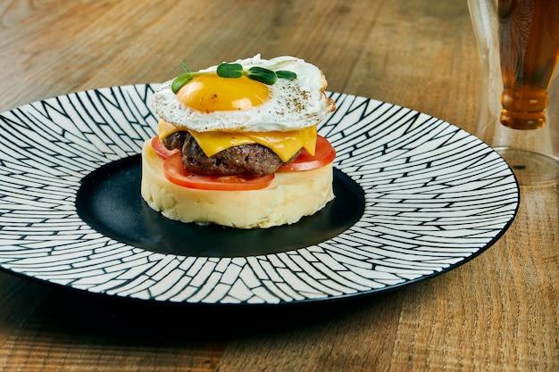 Niezwykłe Danie - Burger Z Tłuczonych Ziemniaków, Pomidorów, Pasztetów Wołowych, Sera Cheddar I Jajek Sadzonych Na Talerzu Ceramicznym. Zamknij Widok Na Jedzenie Premium Zdjęcia