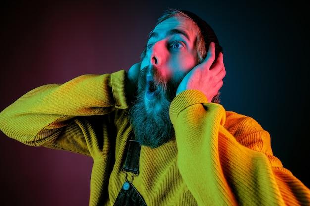 Niezwykle Zszokowany, Zdumiony. Portret Mężczyzny Rasy Kaukaskiej Na Tle Gradientu Studio W świetle Neonu. Piękny Męski Model W Stylu Hipster. Pojęcie Ludzkich Emocji, Wyraz Twarzy, Sprzedaż, Reklama. Darmowe Zdjęcia