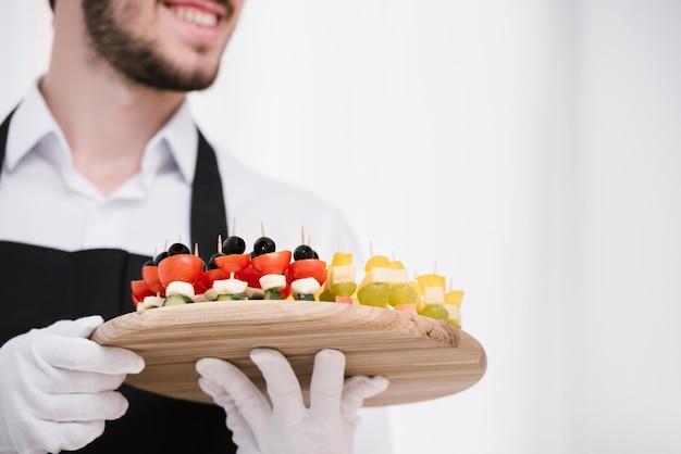 Niski kąt brodaty kelner gospodarstwa przekąski Darmowe Zdjęcia