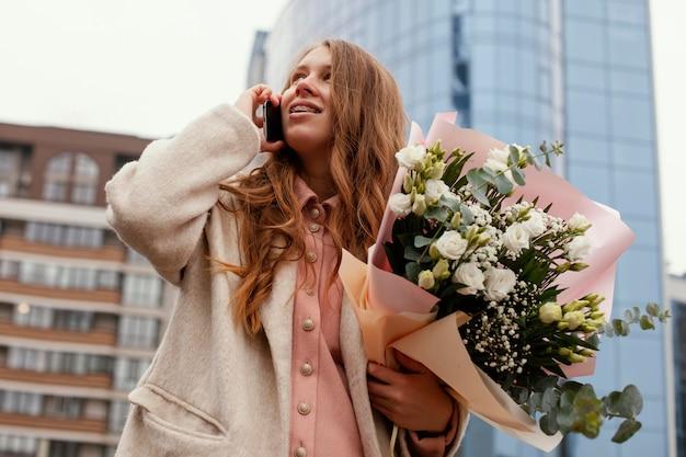 Niski Kąt Eleganckiej Kobiety Na Zewnątrz Rozmawiającej Przez Telefon I Trzymającej Bukiet Kwiatów Darmowe Zdjęcia