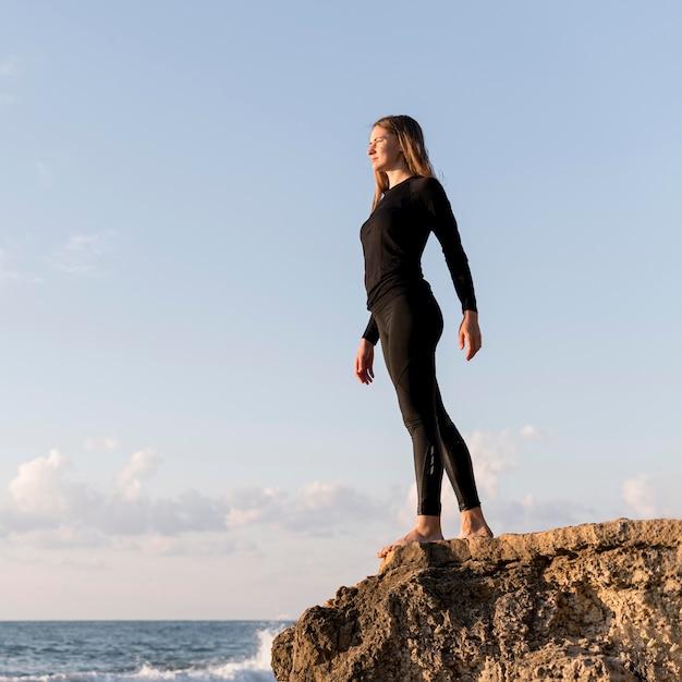 Niski Kąt Kobiety Stojącej I Patrząc Na Morze Darmowe Zdjęcia