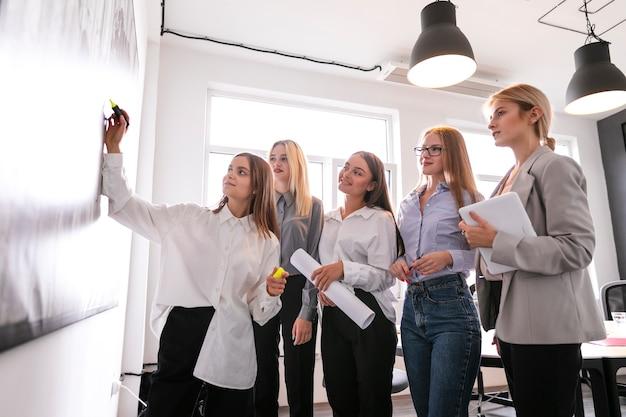 Niski kąt kobiety w czasie burzy mózgów w pracy Darmowe Zdjęcia