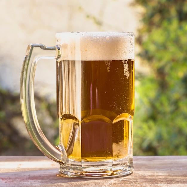 Niski kąt kufel z pieniącym się piwem na stole Darmowe Zdjęcia