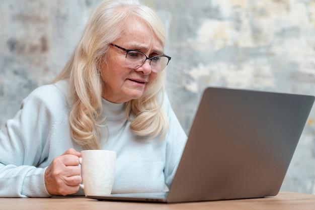 Niski kąt starsza kobieta za pomocą laptopa Darmowe Zdjęcia