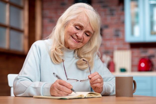 Niski Kąt Starszy Kobieta Pisze W Porządku Obrad Darmowe Zdjęcia