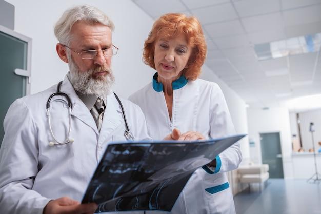 Niski Kąt Strzału Starszy Mężczyzna Lekarz I Jego Koleżanka Bada Skan Mri Pacjenta Premium Zdjęcia