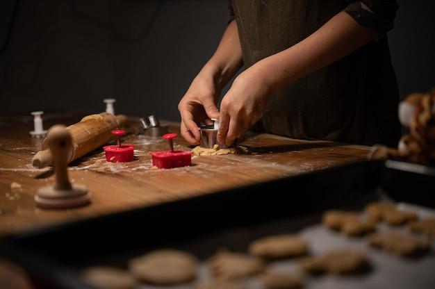 Niski Kąt Widzenia Dziecka Naciskając Foremkę Do Ciastek W Walcowanym Cieście Na Drewnianym Stole. Premium Zdjęcia