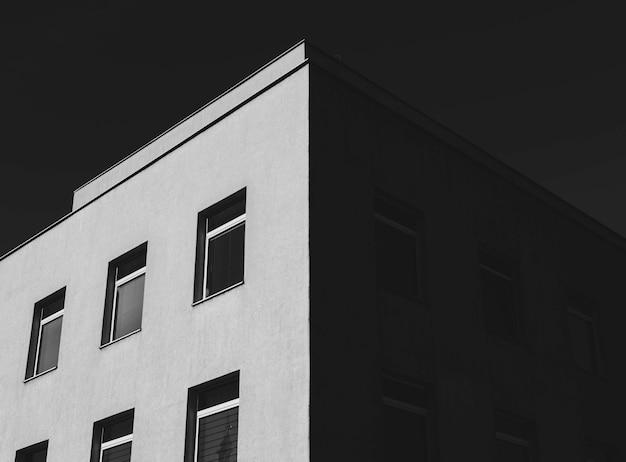 Niskie Ujęcie W Skali Szarości Betonowego Budynku Z Dużą Ilością Okien Pod Ciemnym Niebem Darmowe Zdjęcia