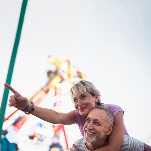 Niskiego kąta szczęśliwa para przy wesołym miasteczkiem Darmowe Zdjęcia