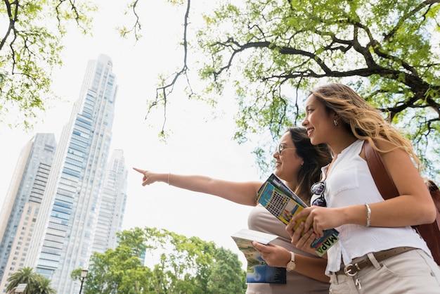 Niskiego kąta widok żeńska mienie mapa w rękach patrzeje jej kobiety wskazuje przy coś Darmowe Zdjęcia