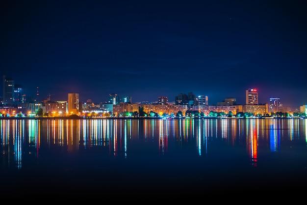 Nocna panorama miasta z wieloma kolorowymi światłami odbijającymi się w wodzie Premium Zdjęcia