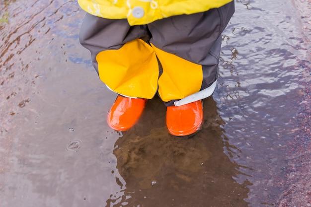 Nogi Dziecka W Pomarańczowych Gumowych Butach Skaczących W Kałużach Jesieni. Jasne Buty Gumowe Dla Dzieci Premium Zdjęcia