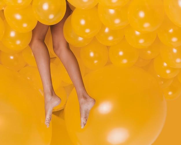 Nogi Kobieta Między Wiele żółtymi Balonami Premium Zdjęcia