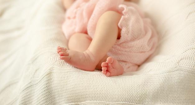 Nogi noworodka owinięte w różowy koc leżący na białym dzianinowym kocu. selektywne ustawianie ostrości. Premium Zdjęcia