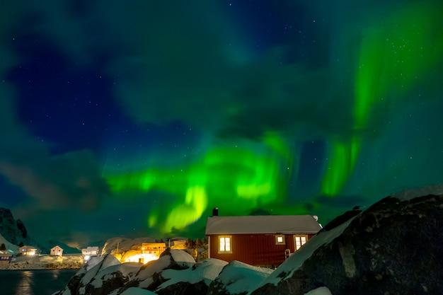 Norwegia. Lofoty. Miasto Hamnoya. Zimowa Noc. Aurora Borealis Nad Dachami Domów Premium Zdjęcia