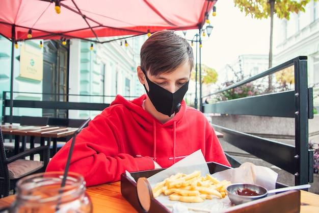 Noszenie Masek W Miejscach Publicznych. Młody Mężczyzna Siedzi W Ulicznej Kawiarni W Masce Ochronnej I Patrzy Na Frytki. Premium Zdjęcia