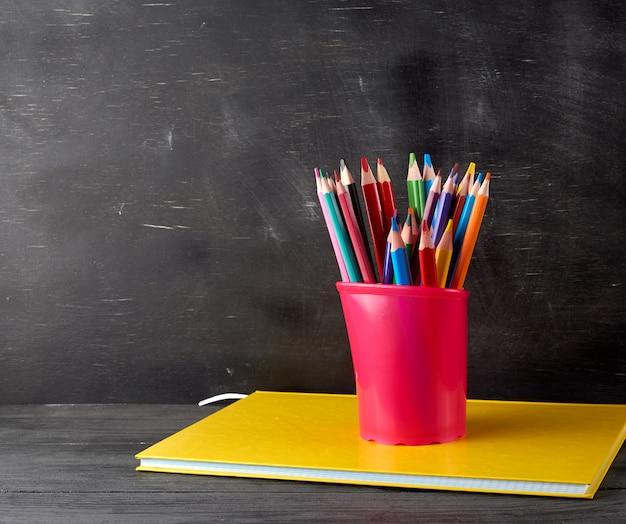 Notatnik, Czarne Szkło Biurowe Z Wielobarwnymi Drewnianymi Ołówkami Premium Zdjęcia