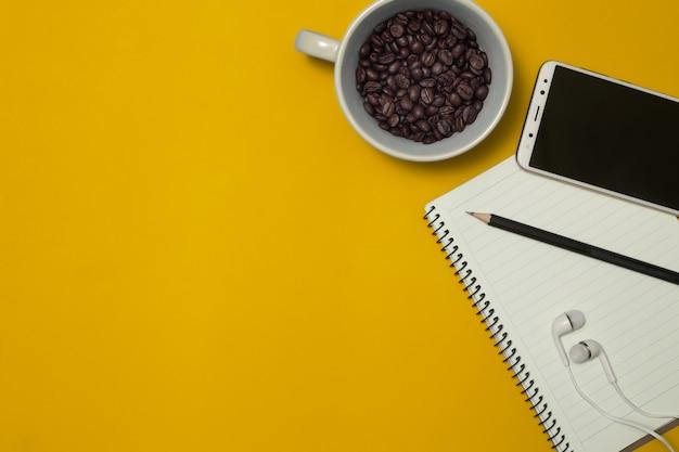 Notatnik I Kawowa Fasola Na Koloru Tle Premium Zdjęcia