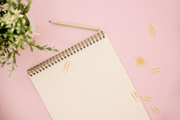 Notatnik i zielona roślina na różowym tle z miejsca na kopię Premium Zdjęcia