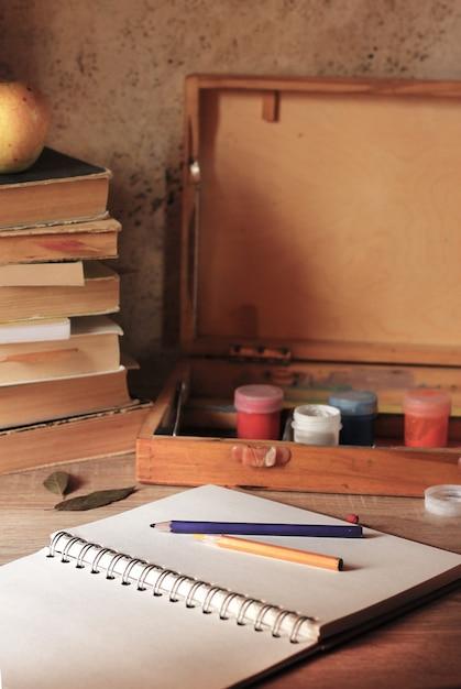 Notatnik leży na stole z farbami Premium Zdjęcia