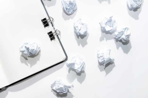Notatnik na białym tle z rozproszonymi zmiętymi notatkami Premium Zdjęcia