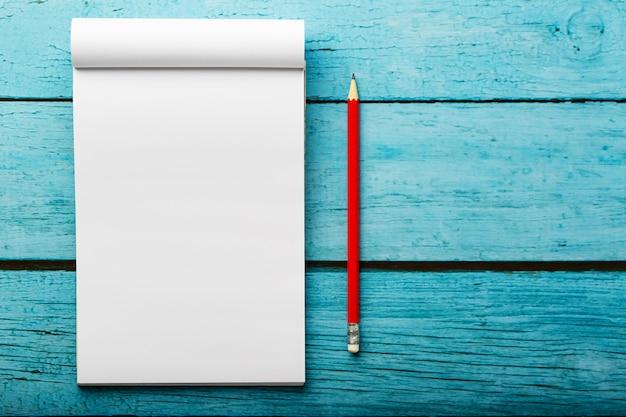 Notatnik z czerwonym ołówkiem na błękitnym drewnianym stołowym tle dla edukaci, pisze celach i czynach Premium Zdjęcia