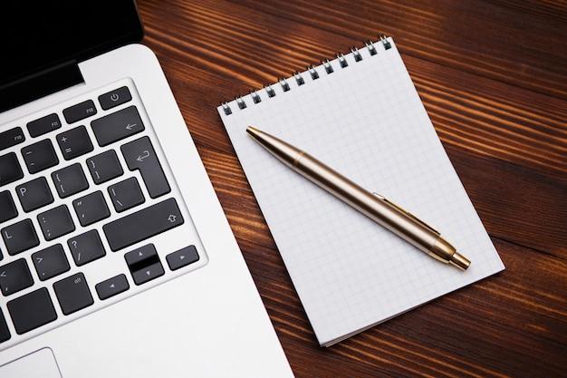 Notatnik Z Długopisem Leży Obok Laptopa Na Drewnianym Stole. Premium Zdjęcia