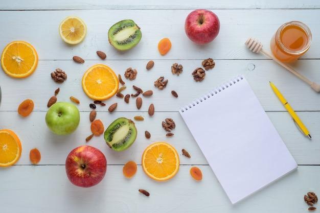 Notatnik Z Długopisem Otoczony Jabłkami, Kiwi, Suszonymi Owocami, Pomarańczami I Jabłkami. Pojęcie Zdrowej Diety I Listy Zakupów. Premium Zdjęcia