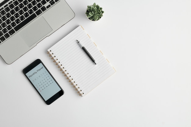 Notatnik Z Długopisem, Planer Miesięczny W Telefonie, Mała Zielona Roślina Domowa W Doniczce I Klawiatura Laptopa Na Białym Tle Premium Zdjęcia