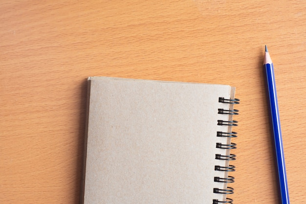 Notepad Z Ołówkiem Na Drewno Deski Tle Używać Tapetę Dla Edukaci, Biznesowa Fotografia Weź Notatkę Produkt Dla Książki Z Papierem I Pojęcia, Przedmiota Lub Kopii Przestrzenią. Premium Zdjęcia