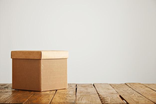 Nowe, Fantazyjne Kwadratowe Pudełko Z Tektury Falistej Z Okładką Na Pięknym Rustykalnym Stole W Studiu O Białych ścianach Darmowe Zdjęcia