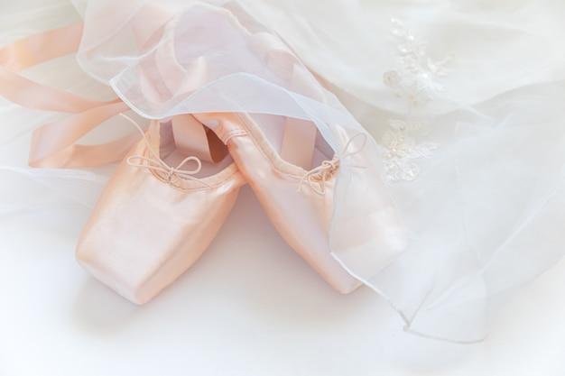 Nowe Pastelowe Beżowe Baletki Z Satynową Wstążką I Tututową Spódnicą Na Białym Stole Premium Zdjęcia