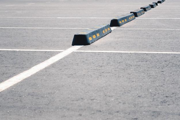 Nowoczesna gumowa bariera dla samochodów na letnim parkingu. Premium Zdjęcia