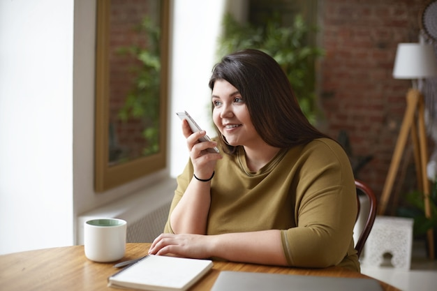Nowoczesna Technologia, Komunikacja I Styl życia. Urocza Piękna Młoda Brunetka Z Krągłym Ciałem Nagrywa Wiadomość Głosową Za Pośrednictwem Komunikatora Internetowego Za Pomocą Telefonu Komórkowego Przy Stoliku Kawiarnianym Darmowe Zdjęcia