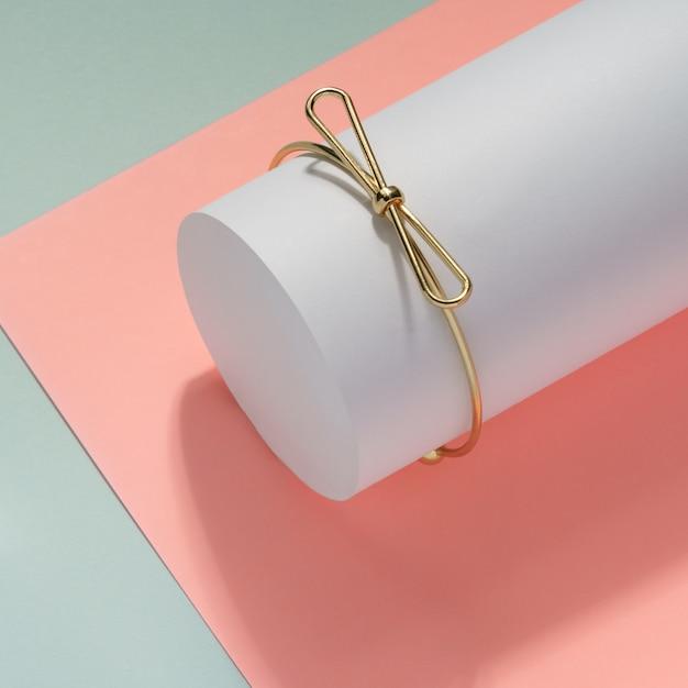 Nowoczesna Złota Bransoletka W Kształcie łuku Na Białym Cylindrze Premium Zdjęcia