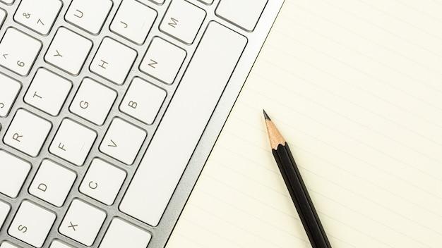 Nowoczesne białe biurko z klawiaturą komputerową, piórem i notatnikiem Premium Zdjęcia