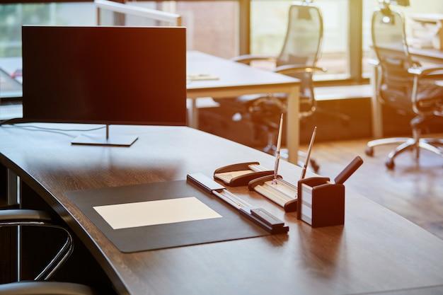 Nowoczesne miejsce pracy w biurze. monitoruj na stole pracowników. biznesowe miejsce pracy dla szefa lub szefa. poranne światło słoneczne. Premium Zdjęcia