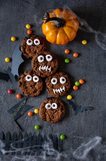 Nowoczesne Tło Halloween. Ciasteczka Halloween. śmieszne Potwory Z Herbatników Z Czekoladą Na Stole Premium Zdjęcia