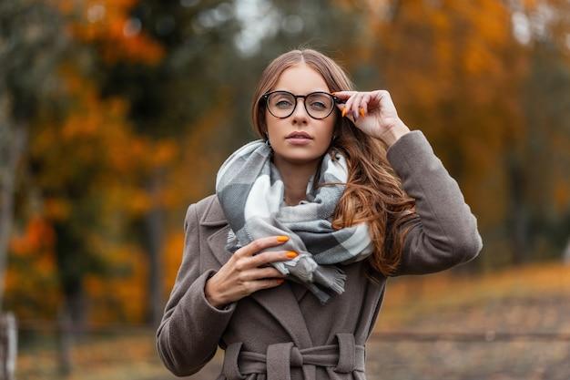 Nowoczesny Modny Model Młodej Kobiety Ze Stylową Fryzurą Prostuje Modne Okulary. Piękne Hipster Dziewczyny W Stylowe Sezonowe Ciepłe Ubrania W Szalik Vintage Pozowanie Na Zewnątrz W Lesie Jesienią. Premium Zdjęcia