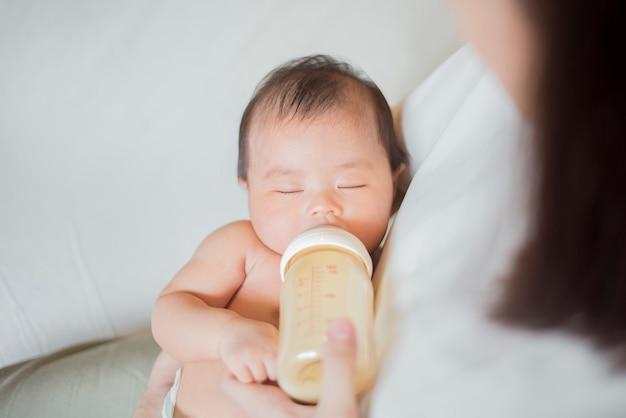 Nowonarodzona dziewczynka pije mleko przez matkę Premium Zdjęcia