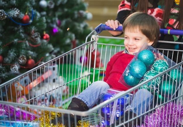 Noworoczne zakupy. dzieciak robi zakupy w supermarkecie ze swoim rodzicem. Premium Zdjęcia