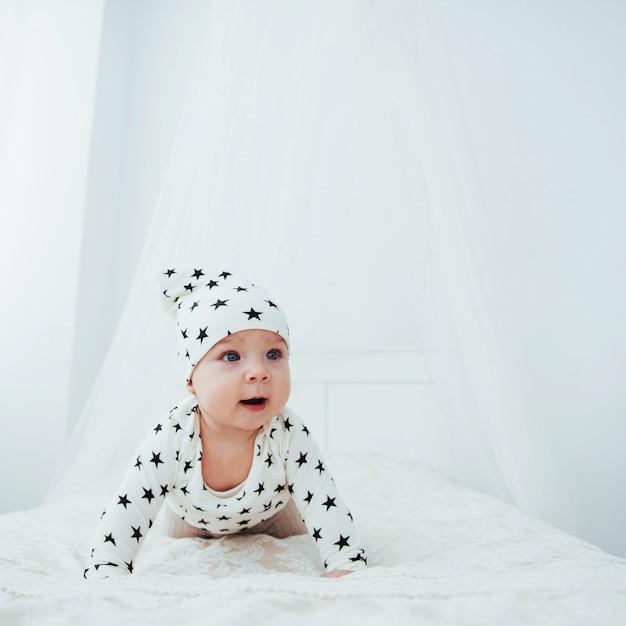 Noworodek ubrany w biały garnitur i czarne gwiazdki to białe miękkie łóżko w studio Premium Zdjęcia