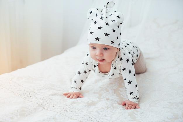 Noworodek Ubrany W Biały Garnitur I Czarne Gwiazdki To Białe Miękkie łóżko Premium Zdjęcia
