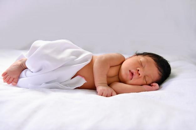 Noworodki śpią w łóżku. dziecko jest w białej sypialni. Premium Zdjęcia