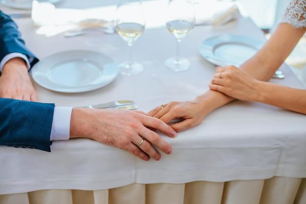 Nowożeńcy Zbliżenie Trzymają Się Za Rękę Przy Stole W Restauracji Z Dwoma Kieliszkami Wina Premium Zdjęcia