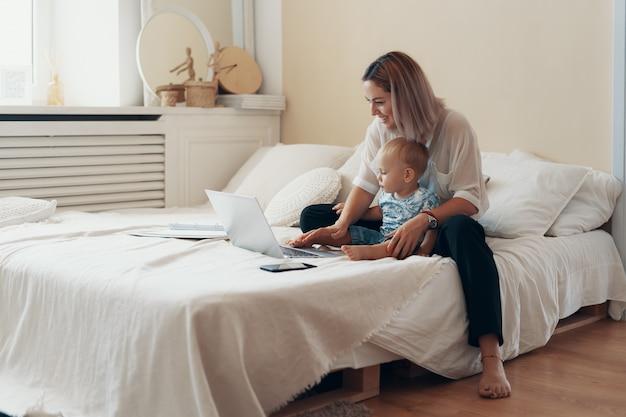 Nowożytna Kobieta Pracuje Z Dzieckiem. Koncepcja Wielozadaniowości, Niezależności I Macierzyństwa Darmowe Zdjęcia