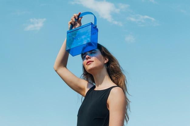 Nowożytna Młoda Kobieta Osłania Jej Oczy Przez Błękitnej Plastikowej Torby Przeciw Niebu Darmowe Zdjęcia