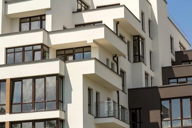 Nowy budynek mieszkalny z tarasowymi balkonami, błyszczącymi oknami i niskim płotem ochronnym na płaskim dachu. Premium Zdjęcia